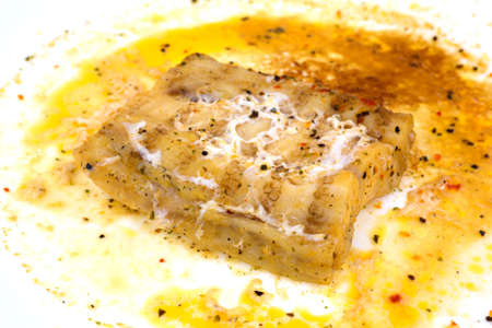 overly: A very close view of a portion of haddock that has been overly microwaved on a white plate.
