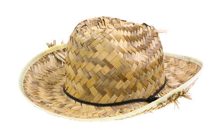 Side view of an old woven straw hat with the straw parting from the brim on a white background.