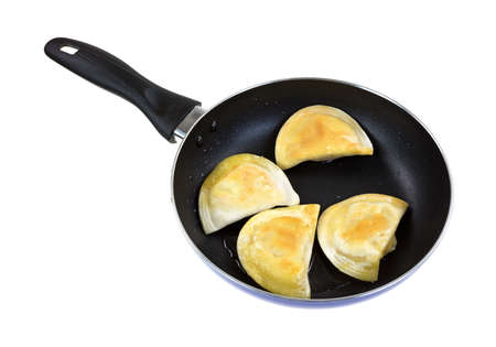browned: Four filled pierogies browned in a black skillet