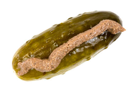 yuck: Top view of a large dill pickle with a line of anchovy paste on a white background.
