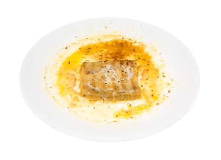overly: A large dish with a small portion of overly microwaved haddock on a white background.