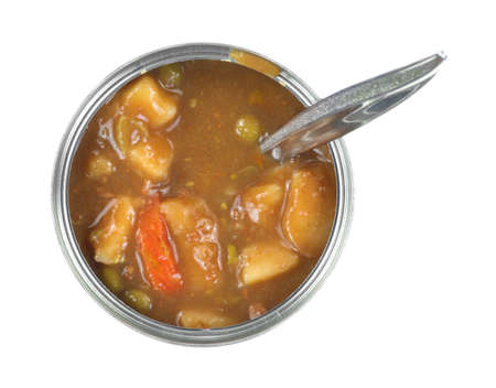 Top view of a tin can of vegetable stew that is opened with a spoon inserted on a white background. photo