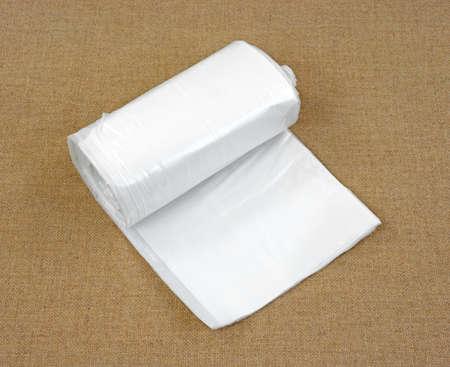 Een licht geopende rol plastic zeil op een tan doek achtergrond. Stockfoto