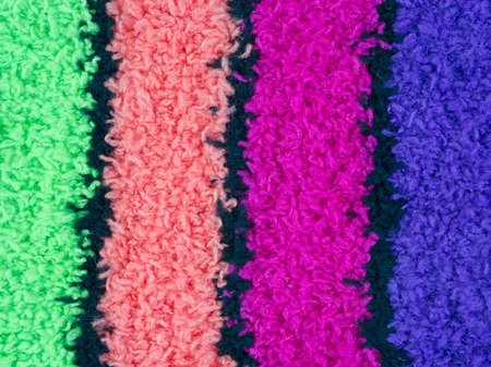 Close view of green, pink, magenta and purple fleece with black stripes. Stock Photo