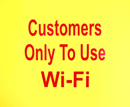 Red lettering of customers only to use wi-fi sign on a yellow background.