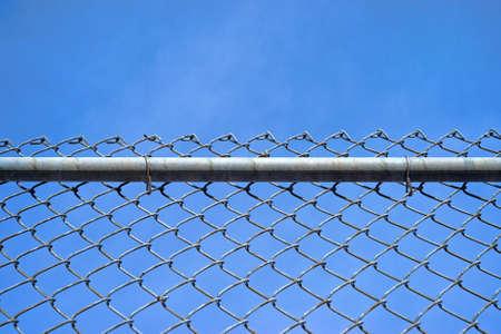 전경이 울창한 바 및 파란 하늘을 묶은 구름이있는 체인 링크 울타리