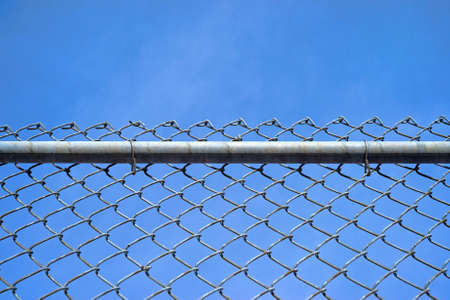 sturdy: A chain link fence with a sturdy bar and fastenings against a blue sky with wispy clouds