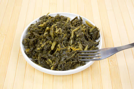 A small serving of collard greens in a dish with a fork Stock Photo - 24265243