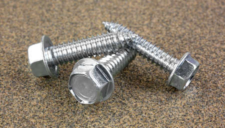 metal fastener: Three hex head cutting screws atop coarse sandpaper. Stock Photo