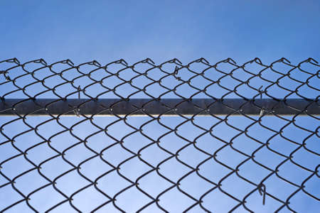 A chain link fence with a sturdy bar behind the mesh and fastenings against a blue sky with wispy clouds