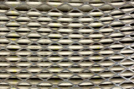 papel filtro: Una vista de cerca del metal y de papel de un filtro de aire del coche sucio