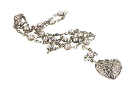 A heart shaped pendant on a silver chain with fake pearls on a white background