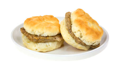 Two very small buttermilk biscuits with sausage patties on a dish