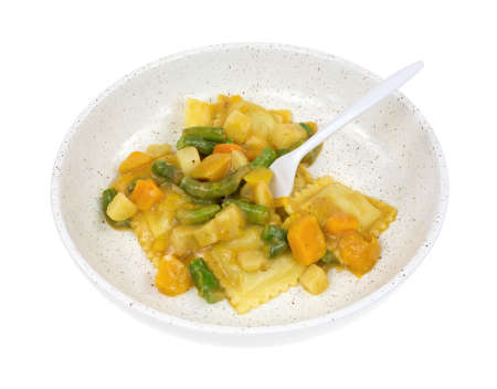 A diet meal of ravioli, butternut squash and green beans in a sauce with a plastic fork in a shallow bowl  Imagens