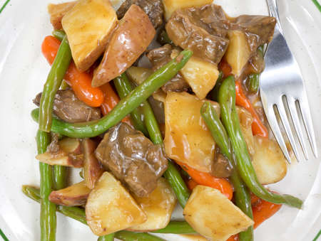 A close view of cooked roasted beef and potatoes with vegetables on a plate with fork. photo