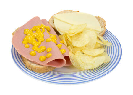bologna baloney: A baloney and provolone cheese sandwich on a blue striped plate with potato chips.