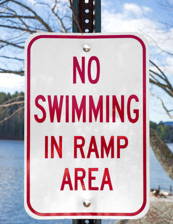 no swimming: A bold No Swimming In Ramp Area sign with water and bly sky in the background  Stock Photo