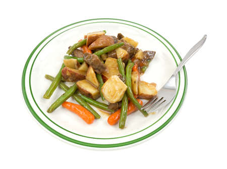 A TV dinner meal of beef and vegetables on a green striped plate with a fork  photo
