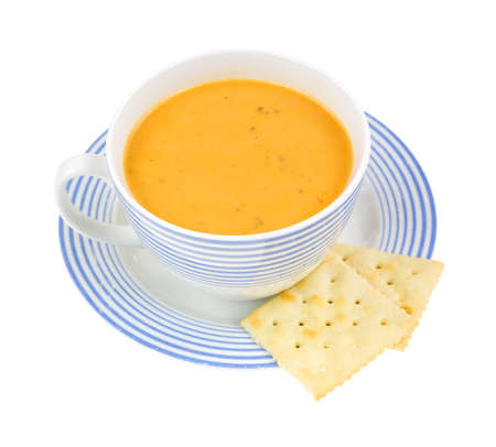 Gouda cheese soup in a coffee cup with two crackers