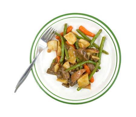Top view of a diet TV dinner of beef and vegetables in a sauce on a green striped plate with fork  photo