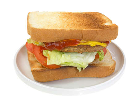 A vegetable burger patty with lettuce tomatoes and onions with mustard on white bread in small dish