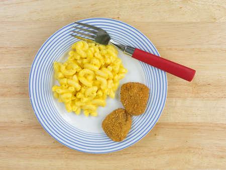 nuggets de pollo: Vista superior de una comida de macarrones con queso con dos nuggets de pollo en un plato de rayas azul con un color rojo manejado el tenedor sobre una mesa de madera