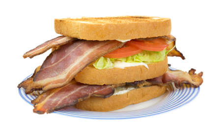 A large bacon lettuce and tomato sandwich on a blue striped plate  版權商用圖片