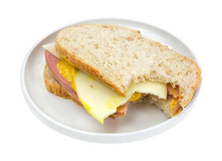 A bitten mortadella with provolone cheese sandwich on a small plate  Stock Photo