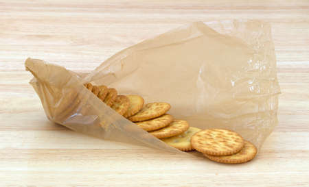 counter top: An opened package of snack crackers in packaging on a wood counter top  Stock Photo
