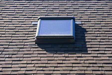 A skylight on an asphalt shingled roof