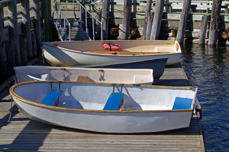dinghies: Three small dinghies on a floating dock