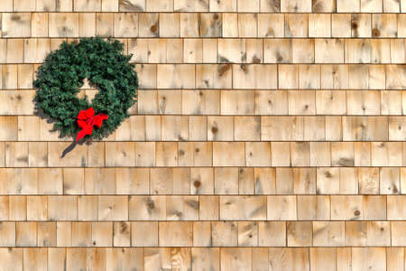 A small holiday Christmas wreath on a cedar shingle wall with a red ribbon