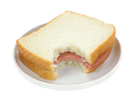 bologna baloney: A bitten baloney sandwich with white bread on a small plate