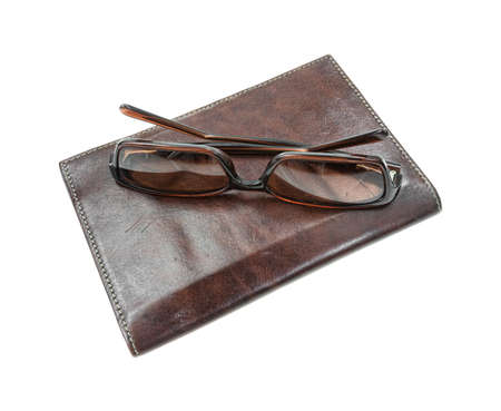 A used pair of sunglasses atop a brown leather billfold on a white background
