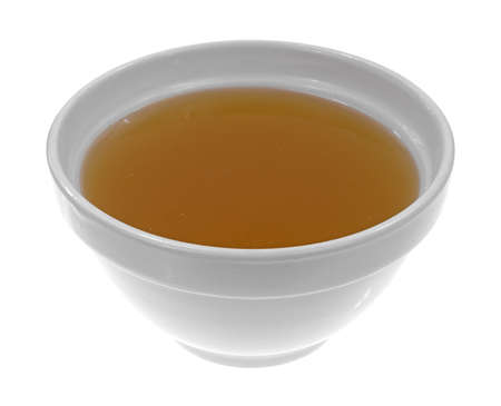 A bowl of clear chicken broth on a white background. Banco de Imagens
