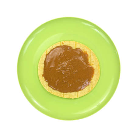 corn tortilla: Top view of a corn tortilla with peanut butter on a green plate atop a white background.