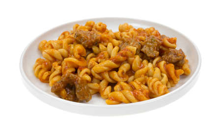 italian sausage: A serving of spiral pasta in a tomato sauce with small chunks of Italian sausage on a small plate.