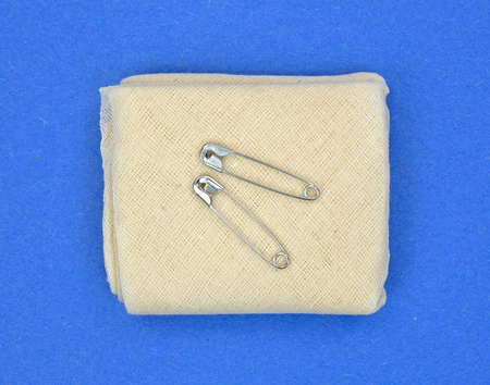 A single folded first aid muslin triangular bandage with two safety pins atop a blue background. Reklamní fotografie