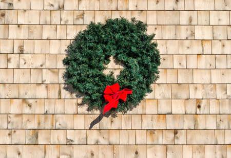 cedar shakes: Un d�a de fiesta Guirnalda de la Navidad en una pared de rocas de cedro madera.