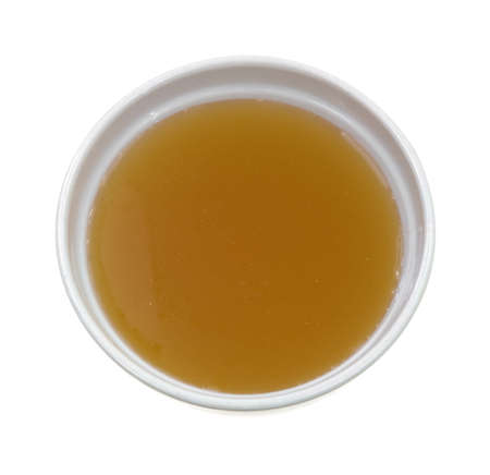Top view of a bowl filled with clear chicken broth on a white background.