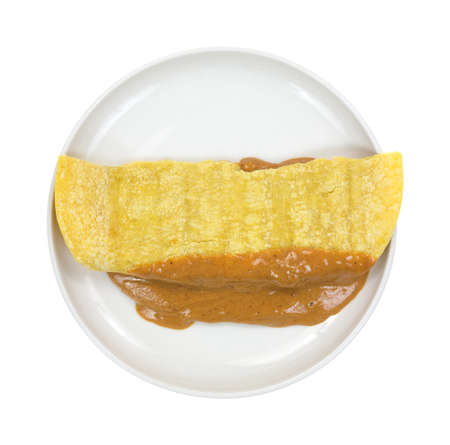 corn tortilla: Top view of a small plate with a folded corn tortilla filled with peanut butter  Stock Photo