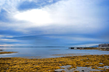 Dark and stormy skies above low water in Searsport, Maine