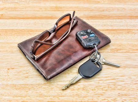 車のキーと彩色のサングラスの木製卓上に茶色の革財布頂上セット 写真素材