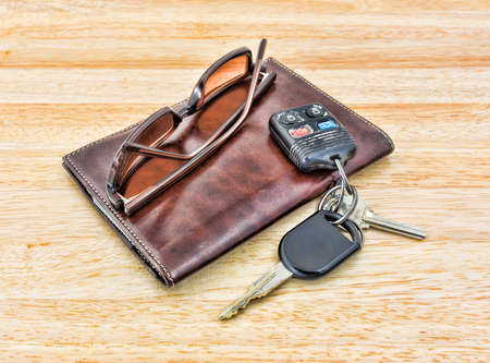 A set of car keys and tinted sunglasses atop a brown leather wallet on wood tabletop