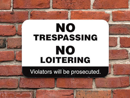 loitering: A bold no trespassing no loitering sign attached to an old brick wall  Stock Photo