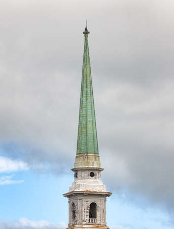 spire: An old metal covered church spire in the foreground with clouds and sky in the background