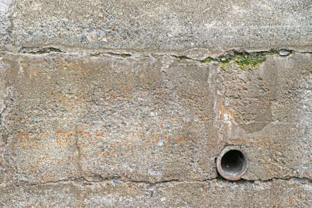 retaining: An old exterior retaining wall with a clay drainpipe and surface cracks with algae  Stock Photo