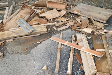 A large amount of discarded home repair lumber and cabinet doors on top of old asphalt