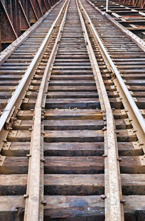 creosote: A set of railroad tracks leading into the distance over a rusty bridge