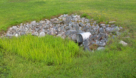 culvert: A stainless steel drainage culvert surrounded by rocks and green grass  Stock Photo